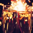 Stock Photo: Champagne glass against christmas sparkler background