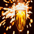 Champagne glass against christmas sparkler background — Stock Photo #35133277