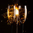 Champagne glasses against christmas sparkler background — Stock Photo