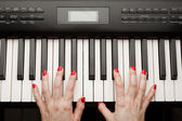 Hands playing digital piano synthesizer — Stock Photo