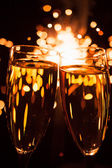 Champagne glass against christmas sparkler background — Stok fotoğraf