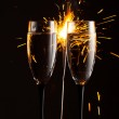 Champagne glasses against christmas sparkler background — Stock Photo #36567871