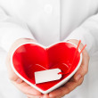 Red heart shape with empty label in hands — Stock Photo #37003285