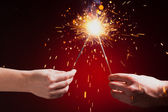 Sparklers in hands — Stock Photo