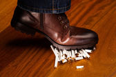 Shoes trampling down on cigarettes — Stock Photo