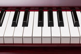 Ebony and ivory keys of red piano — Stock Photo