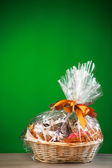 Gift basket against green background — Stock Photo