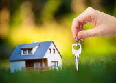 Hand holding key against house background — Stock Photo