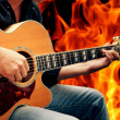 Man playing guitar against fire background — Stock Photo #46263629