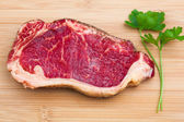 Fresh marbled meat on a wooden hardboard — Stock Photo