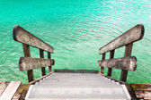 Wooden banister of the pier with water — Stock Photo