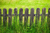 Village decorative fence against green lawn background — Stock Photo
