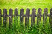 Dorp decoratieve omheining tegen groen gazon achtergrond — Stockfoto