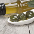 Virgin olive oil and green olives — Stock Photo