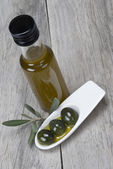Olive oil and olives on a wooden surface — Stock Photo