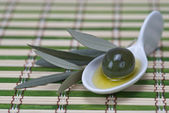Olive in a china spoon — Stock Photo
