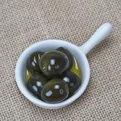 Schotel met olijven op een jute — Stockfoto
