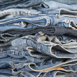 Stack of different old worn blue jeans — Stock Photo