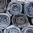 Rolls of different worn blue jeans stacked — Stock Photo #14704489
