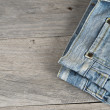 Stock Photo: Old worn jeans over wooden background