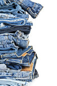 Stack of blue jeans over a white background — Foto de Stock