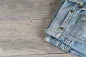 Old worn jeans over a wooden background — Stock Photo