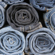 Rolls of different worn blue jeans stacked — Stock Photo