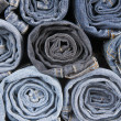 Stock Photo: Rolls of different worn blue jeans stacked