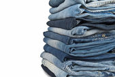Stack of blue jeans over a white background — Stock Photo