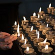 Lighting candles in a church — Stockfoto