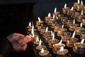 Lighting candles in a church — Stock Photo