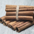 Stock Photo: Cinnamon sticks on a wooden background