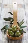 Wooden spoon with olives and oil — Stock Photo