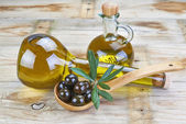 Smart bottle of olive oil and spoon with olives — Stock Photo