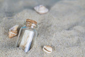 Message in a bottle on the sand of th beach — Stock Photo