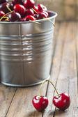 Little brass bucket of cherries on a table — Stock Photo