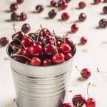 Little brass bucket of cherries on a table — Stock Photo #48343145