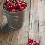 Little brass bucket of cherries on a table — Stock Photo #48343335