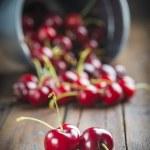 Little brass bucket of cherries on a table — Stock Photo #48343777
