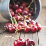 Little brass bucket of cherries on a table — Stock Photo #48344411