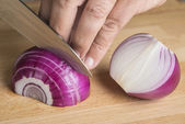 Chef choppig a red onion with a knife — Stockfoto