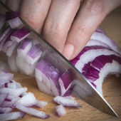 Chef choppig a red onion with a knife — Stock fotografie
