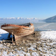 Old lonely boat abandoned at snowy coast — Stock Photo