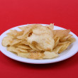 Potato chips on red back  — Stock Photo