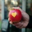 Man's hand hold a red apple with heart — Stock Photo