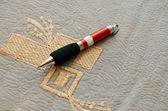Pen on gold embroidery — Zdjęcie stockowe