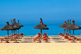 Tropical beach scenery with parasol and deck chairs. umbrella a — Stockfoto