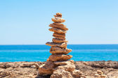 Balanced stones, pebbles stacks against blue sea. — Stock Photo
