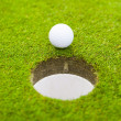 Stock Photo: Golf ball on lip of cup.
