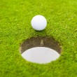 Golf ball on lip of cup. — Stock Photo #30282075